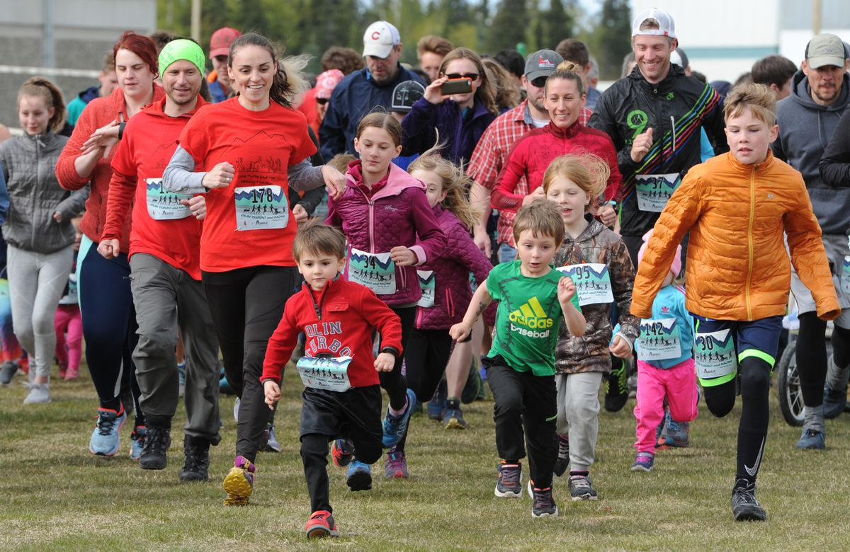 """Four-year-old Olin """"Turbo"""" Ahonen, in red, sprints from the starting line of the inaugural Olin Turbo and Mom Family Fun Run on Mother's Day at Service High. He is followed closely by his mother, Mary Ahonen, and father, Adam Ahonen, also wearing red. (Bill Roth / ADN)"""