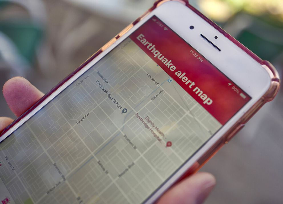 A mobile phone customer looks at an earthquake warning application on an iPhone in Los Angeles. (AP Photo/Richard Vogel, File)