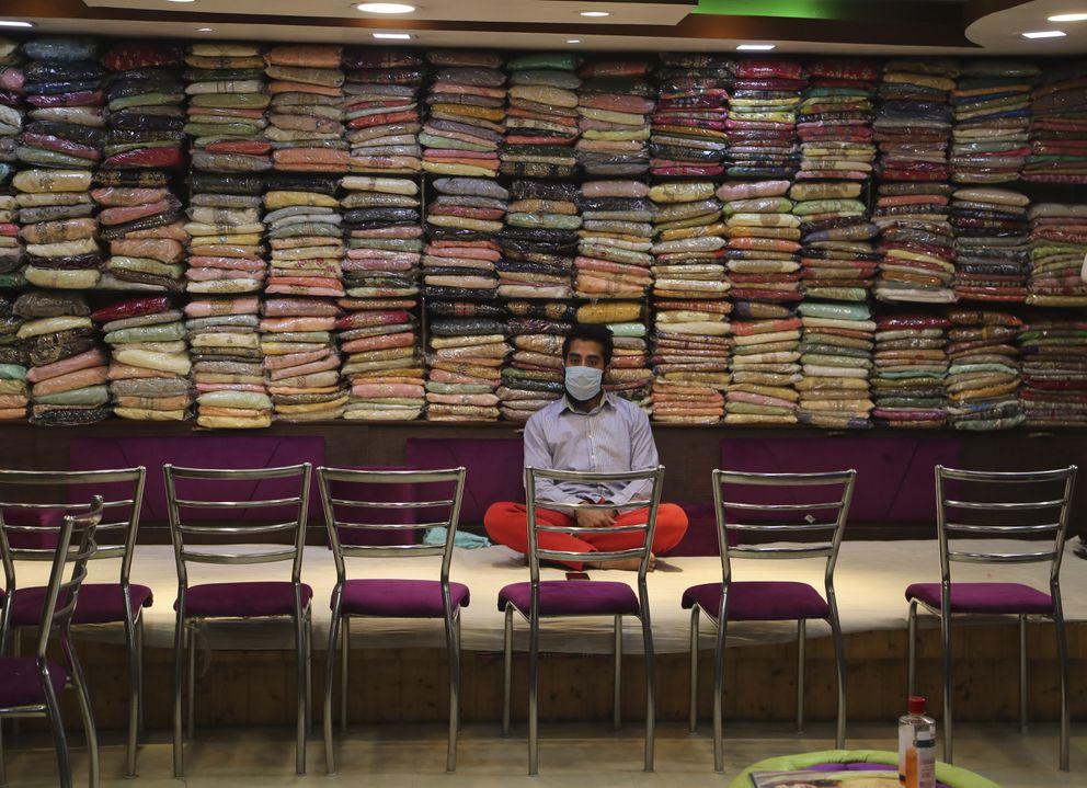 A Kashmiri shopkeeper wearing a mask waits for customers ahead of Eid al-Fitr during a nationwide lockdown to control the spread of coronavirus, in Srinagar, Indian controlled Kashmir, Wednesday, May 20, 2020. (AP Photo/Mukhtar Khan)