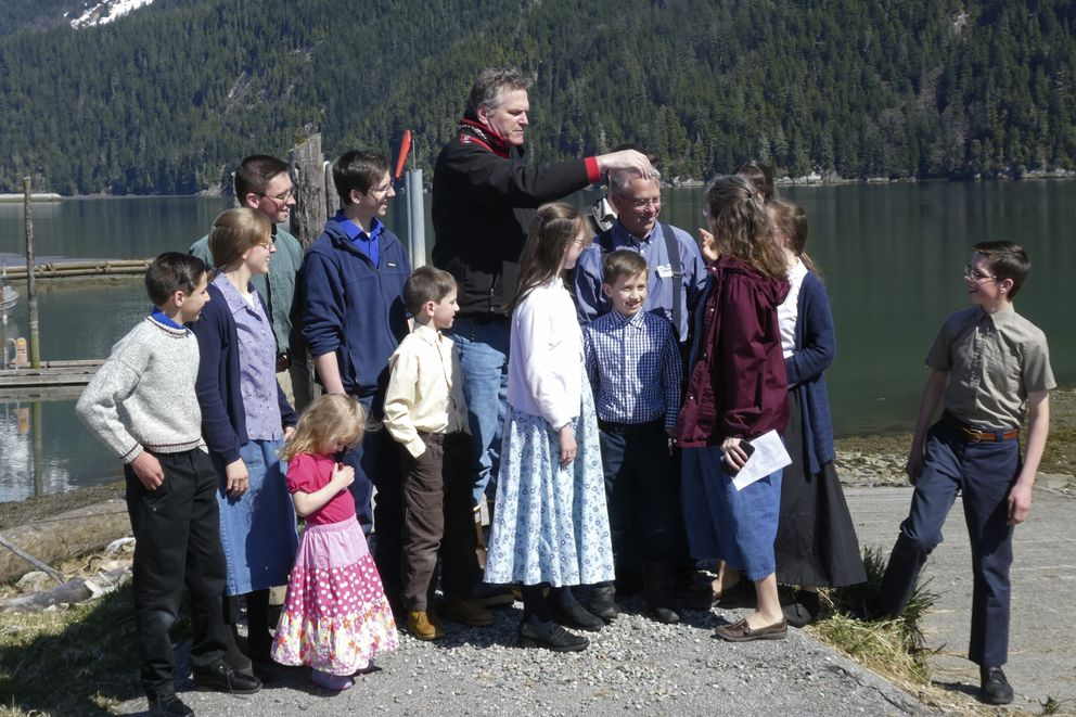 Alaska Gov. Mike Dunleavy, center, gathers with members of Mark and Amy Bach's family as they prepare to pose for a photo on Thursday, April 22, 2021, in Hyder, Alaska. The family also invited Dunleavy to their home before he left Hyder, a small community near the U.S.-Canada border and one of the stops on Dunleavy's one-day visit to southeast Alaska communities on April 22, 2021. (Becky Bohrer / Associated Press)