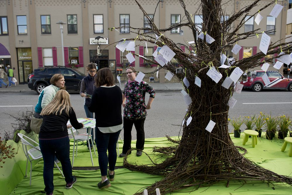 Visitors fill out cards with their wishes for Anchorage and attach them to a tree created by the Anchorage chapter of the American Society of Landscape Architects at their Park(ing) Day location on G Street. About a dozen organizations participated in Park(ing) Day in downtown Anchorage on Friday, September 15, 2017. The event, held in various locations in the U.S. and beyond on the third Friday in September, invites individuals and groups to reimagine and design a public space in a parking spot. In Anchorage, about a dozen parking spaces were transformed. Easy Park created a deck out of pallets, City Hall hosted a Welcoming Anchorage tent that handed out tea, and the Alaska Humanities forum set up a camp site and shared Pilot Bread, to name a few. (Marc Lester / Alaska Dispatch News)