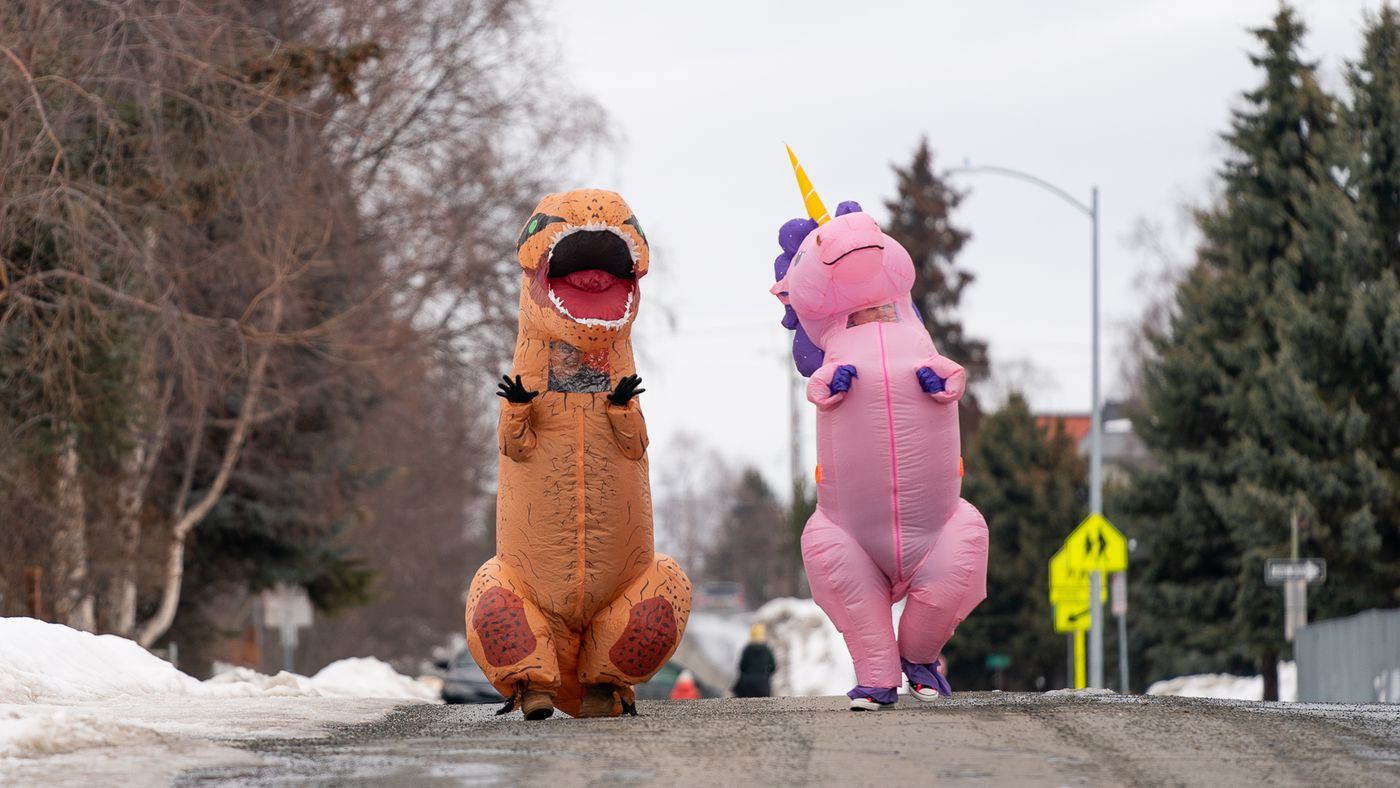 MARCH 25. Christine Hohf, wearing a unicorn costume, and Andi Correa, wearing a dinosaur costume, walk through South Addition. Hohf, who works as a scrub tech at a surgery center, said her hours were cut due to elective surgeries being put off because of the coronavirus pandemic, and she wanted to do something that would make people smile. (Loren Holmes / ADN)