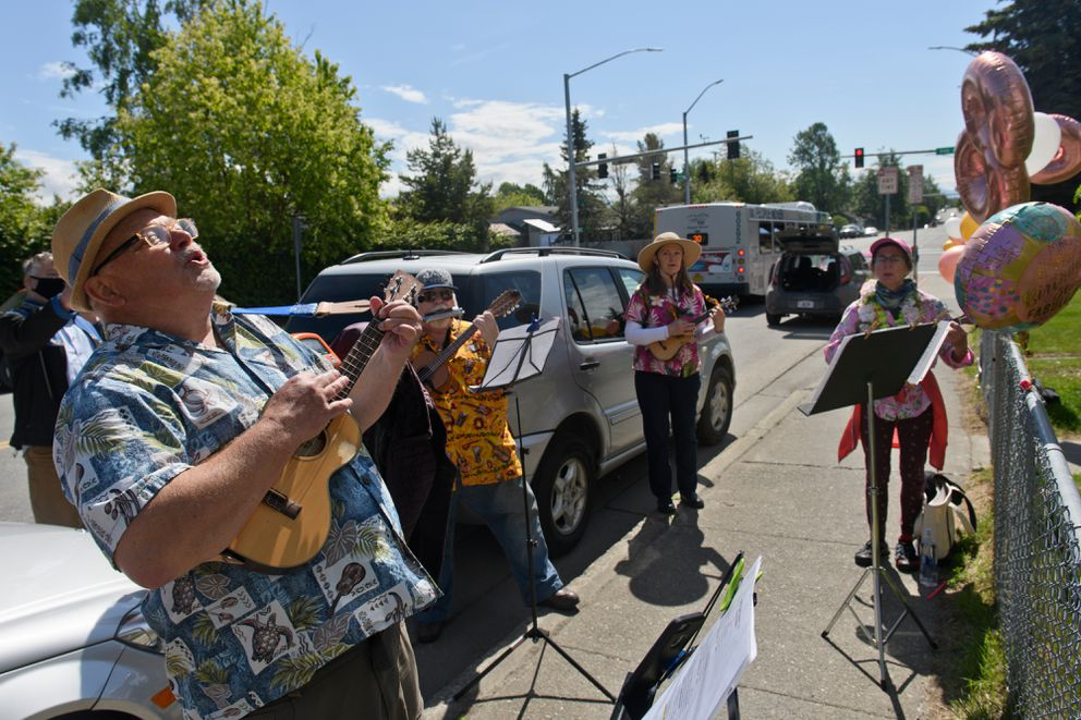 Scott Taylor, left, and other ukulele players from the Alaska Jumping Flea Society sing to Marge Tomsic on her 98th birthday. (Marc Lester / ADN)