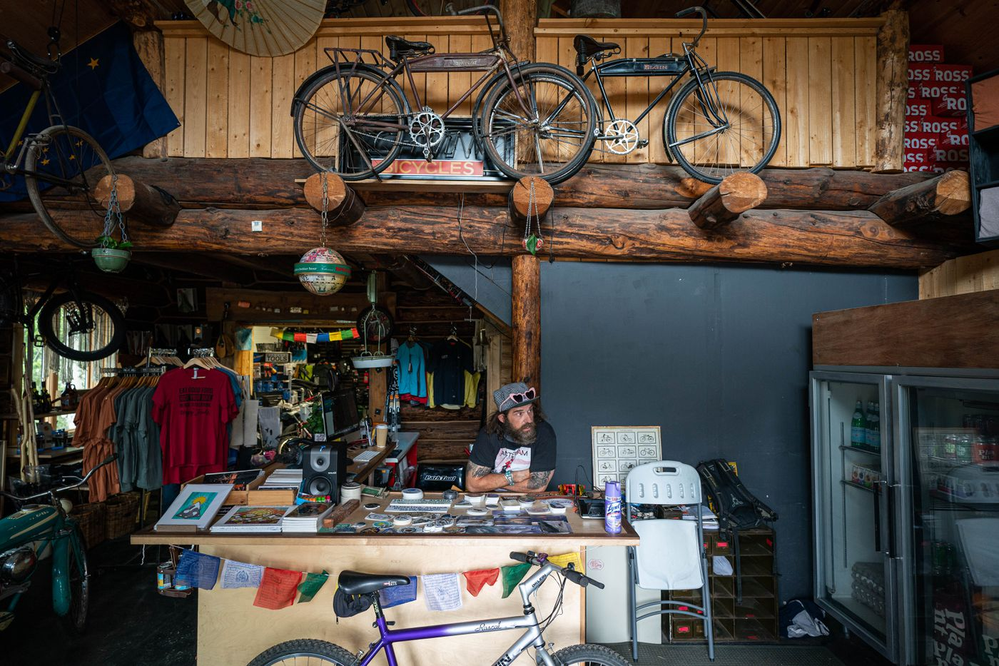 North Shore Cyclery owner Shawn Thelen sits at the counter in his bicycle shop on Thursday, May 21, 2020 in Talkeetna. (Loren Holmes / ADN)
