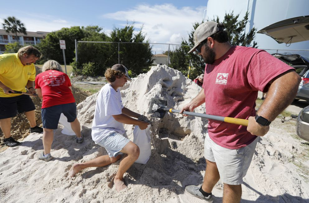 Walker Townsend, at right, from the Isle of Palms, S.C., fills a sand bag while Dalton Trout, in center, holds the bag at the Isle of Palms municipal lot where the city was giving away free sand in preparation for Hurricane Florence at the Isle of Palms S.C., Monday, Sept. 10, 2018. (AP Photo/Mic Smith)
