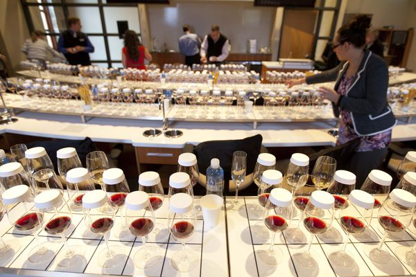 Teams of sommeliers fill and cover glasses preparing for the Legends of Napa Valley wine tasting event of