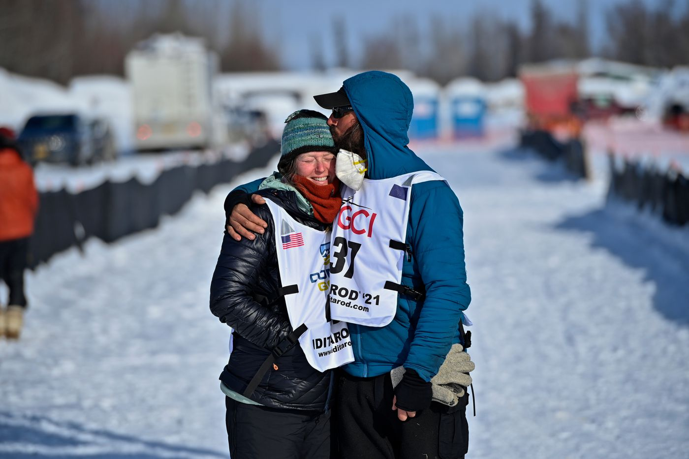 Paige Drobny gets a kiss from her husband Cody Strathe at the Iditarod finish line in Willow on March 16, 2021. Drobny finished 19th and Strathe finished 20th in the 2021 Iditarod. (Marc Lester / ADN)