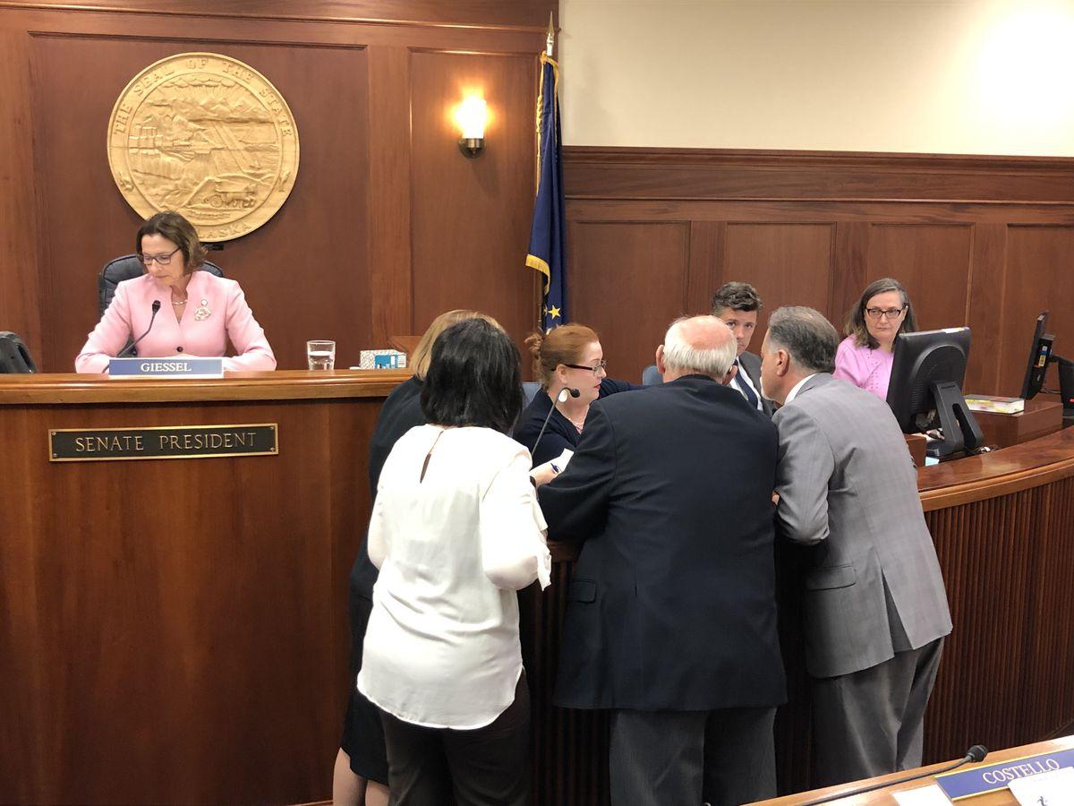 Members of the Alaska Senate crowd around Senate Secretary Liz Clark for an interpretation of the Senate rules Thursday, June 6, 2019. (James Brooks / ADN)