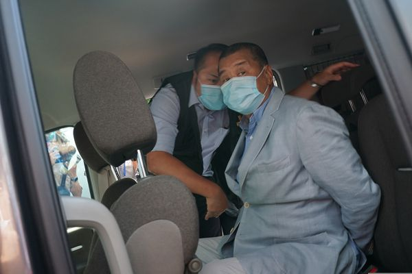 Hong Kong media tycoon Jimmy Lai, right, who founded local newspaper Apple Daily, is arrested by police officers at his home in Hong Kong, Monday, Aug. 10, 2020. Lai was arrested Monday on suspicion of collusion with foreign powers, his aide said, in the highest-profile use yet of the new national security law Beijing imposed on the city after protests last year. (AP Photo)
