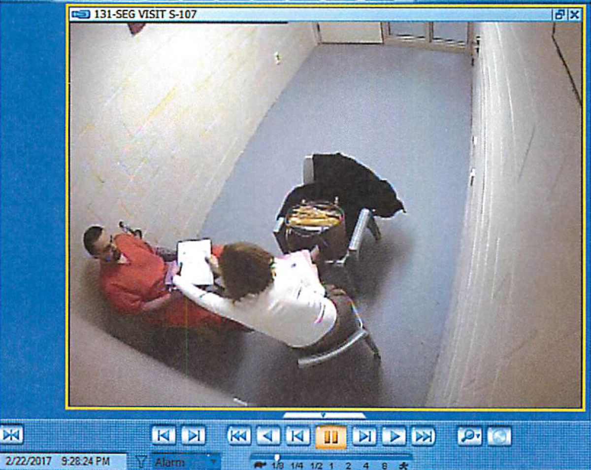 A video frame alleges concealment of contraband as attorney Kit Lee Karjala visits inmate Christopher Brandon Miller at Anchorage Correctional Complex. Both face federal charges in a scheme to deliver drugs to the jail. (Alaska Dept. of Corrections)