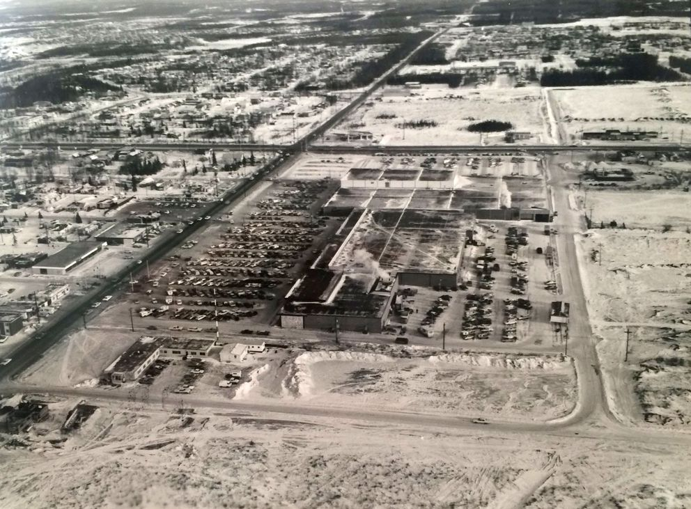 Aerial photo from the Mall's opening in 1968. This view looks roughly east. The west end of the mall is closest to the camera. Northern Lights Boulevard runs from the lower left side of the frame back. The (now) Seward Highway is on the east side of the mall. Benson and Denali look to be unpaved, short streets. (Photo by Ward Wells, provided by Midtown Mall)