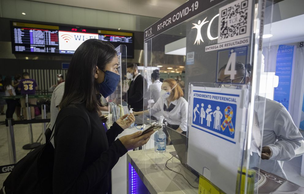 A woman asks a health worker about COVID-19 tests in the Guarulhos airport, near Sao Paulo, Brazil, as she waits for her connecting flight to Buenos Aires, Argentina, on Saturday, Dec. 12, 2020. (AP Photo/Andre Penner)