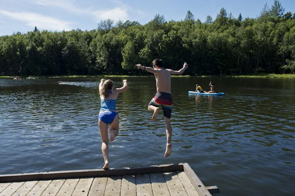 Sierra Hymas and Bryson Noble take the plunge into Little Campbell Lake off the dock on a warm and sunny August 4, 2017. (Marc Lester / Alaska Dispatch News)