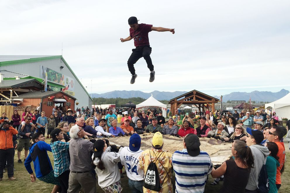 Byron Nicholai of Toksook Bay is flung into the air in the blanket toss at the Gathering Place on Saturday evening, September 3, 2016, at the Alaska State Fair in Palmer. Nicholai, who just finished high school, is known for mixing traditional and modern music on YouTube and on his Facebook page I Sing. You Dance. (Erik Hill / Alaska Dispatch News)