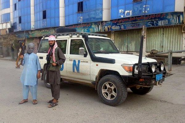 In this Sept. 29, 2015 file photo, Taliban fighters pose for a photo next to a UN vehicle they plundered in Kunduz, Afghanistan.