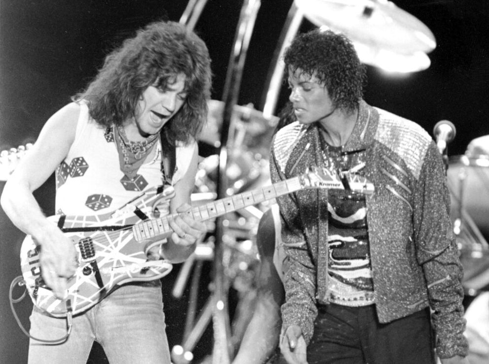 FILE - This July 14, 1984 file photo shows Van Halen guitarist Eddie Van Halen, left, performing 'Beat It ' with Michael Jackson during Jackson's Victory Tour concert in Irving, Texas. Van Halen, who had battled cancer, died Tuesday, Oct. 6, 2020. He was 65. (AP Photo/Carlos Osorio, File)