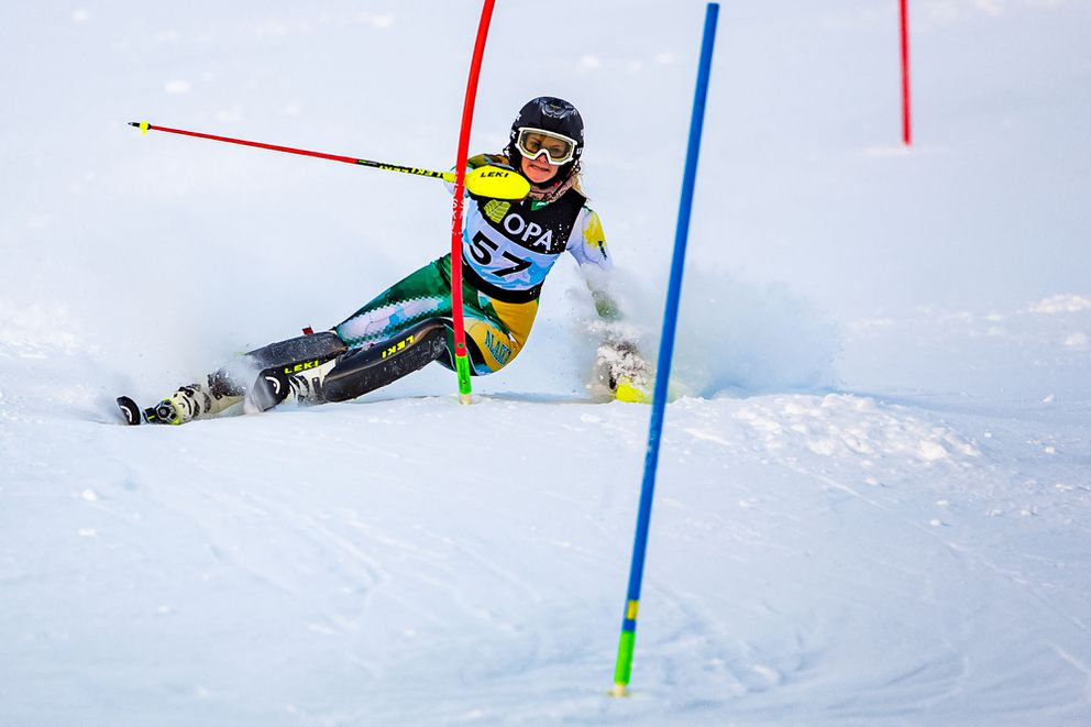 Race winner Rebecca Fiegl of UAA negotiates a gate on highly edged skis while looking ahead to the ones. (Photo by Bob Eastaugh)