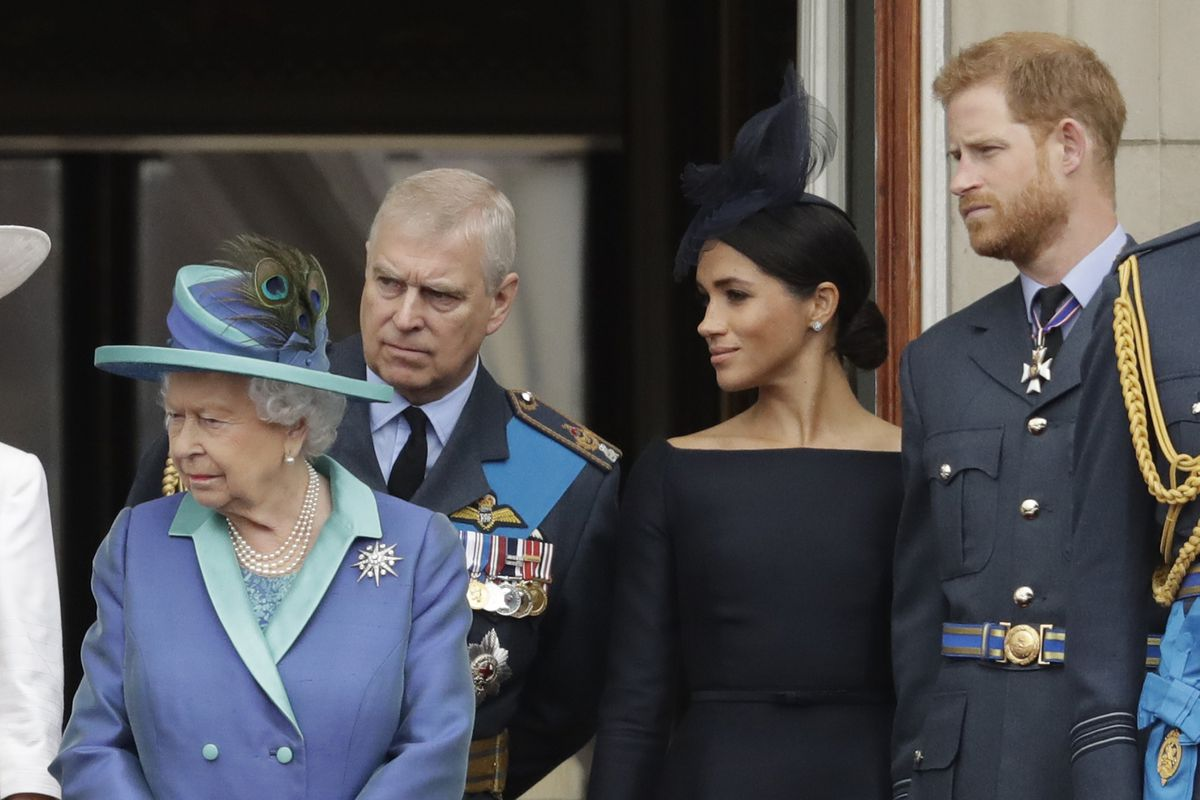 FILE - In this Tuesday, July 10, 2018 file photo Britain's Queen Elizabeth II, Prince Andrew, Meghan the Duchess of Sussex and Prince Harry stand on a balcony to watch a flypast of Royal Air Force aircraft pass over Buckingham Palace in London. (AP Photo/Matt Dunham, File)