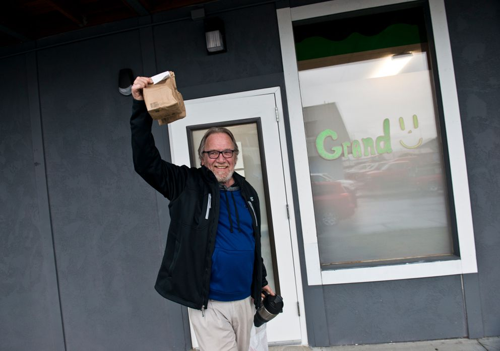 Michael Holcombe holds his first Herbal Outfitters purchase aloft. Holcombe was the marijuana retailer's first customer. Marijuana retailer Herbal Outfitters opened its doors to customer for the first time in Valdez on Saturday, October 29, 2016. (Marc Lester / Alaska Dispatch News)