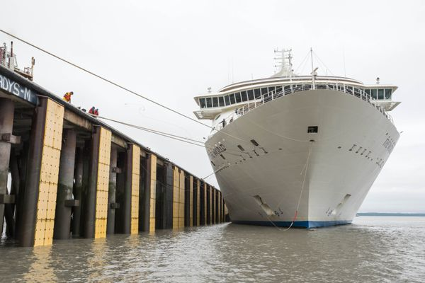 Crew members from The World, a high-end residential cruise ship, toss a line to longshoremen as the ship docks at the Port of Anchorage Thursday, Aug. 3, 2017. (Loren Holmes / Alaska Dispatch News)
