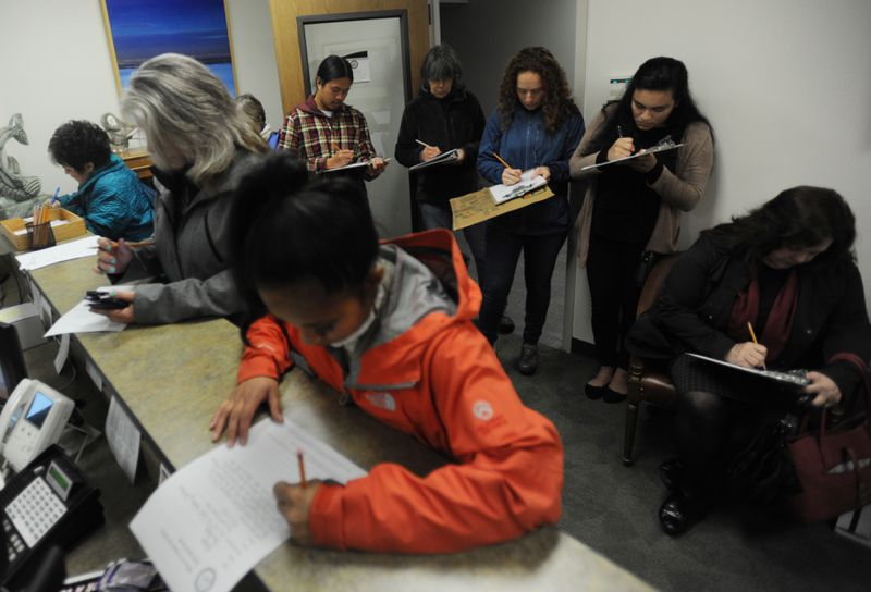 """DACA supporters fill out public opinion messages in Sen. Dan Sullivan's Anchorage office on Tuesday in the wake of President Trump's announcement to end protection for hundreds of thousands of """"dreamers,"""" children who were brought to the U.S. and have been living here illegally. (Bill Roth / Alaska Dispatch News)"""