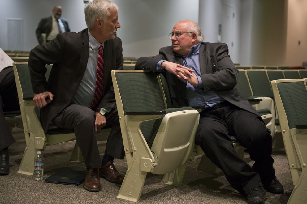Jim Kubitz, left, rises to voice his support for Ira Perman, right, after both men were tied in several rounds of voting by Anchorage Assembly members. (Marc Lester / ADN)