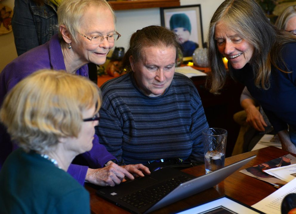 """Denise Martin, left, Gail Irvine, center left, and Jan Myers, right, of Sherri Hadley's """"Glacial Erratics"""" Share the Care group review photos from a celebration of life held for Hadley, center right, two weeks earlier on Tuesday at herassisted living home in Anchorage. (Erik Hill / Alaska Dispatch News)"""