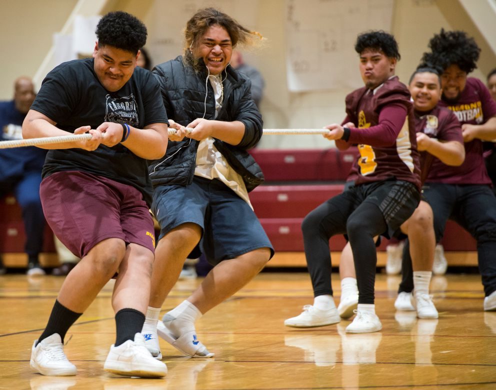 From left, Rolan Peau and Iese Sala help lead their tug-o-war team to victory. (Marc Lester / Anchorage Daily News)