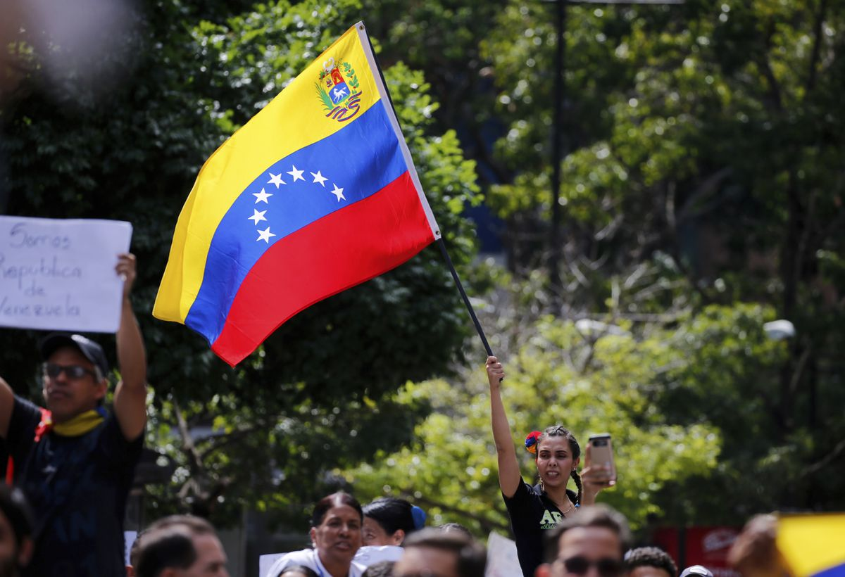 A demonstrator waves a Venezuelan flag during a walk out against President Nicolas Maduro, in Caracas, Venezuela, Wednesday, Jan. 30, 2019. Venezuelans are exiting their homes and workplaces in a walkout organized by the opposition to demand that Maduro leave power.(AP Photo/Fernando Llano)