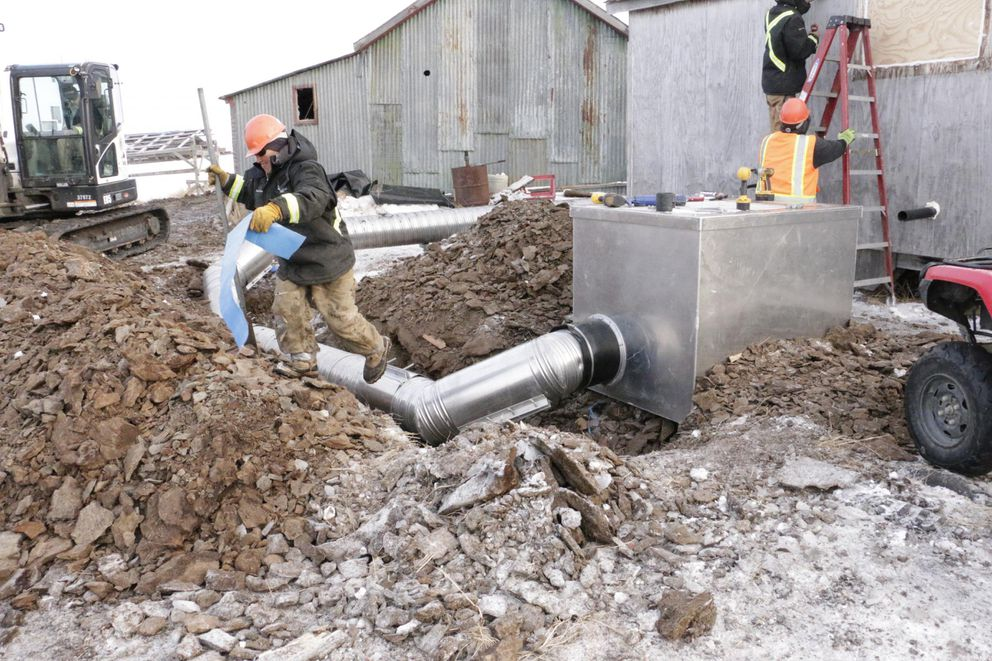 ANTHC workers install a water and sewer system to an Eek home on February 21, 2019. (Anna Rose MacArthur / KYUK)