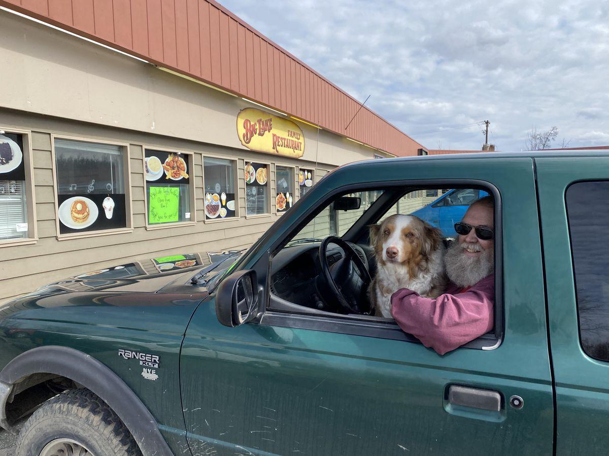 Denis Watters and his Australian shepherd Sasha wait for a takeout order at Big Lake Family Restaurant on Friday. Watters had hoped to go inside to eat, but needed a reservation under new COVID-19 policies. (Zaz Hollander / ADN)