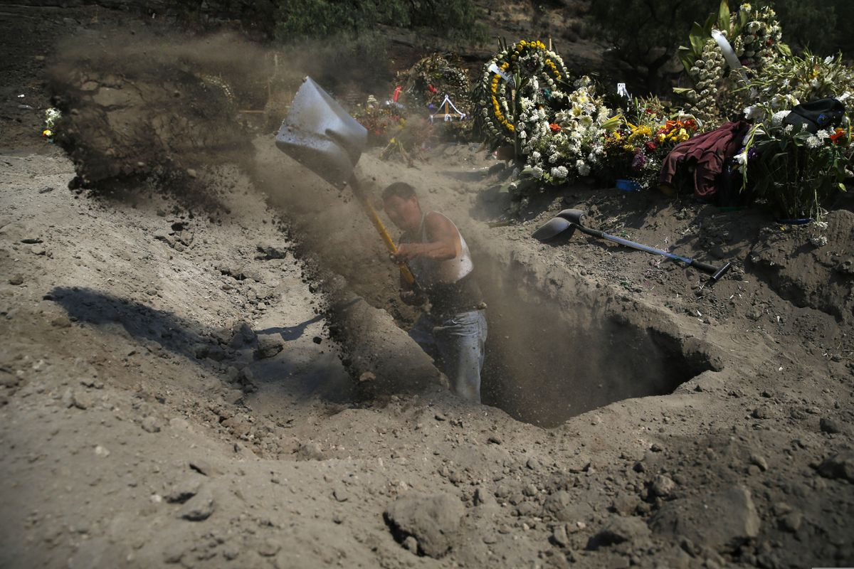 A worker digs a new grave at a newly inaugurated plot at the Valle de Chalco Municipal Cemetery, built to accommodate the rise in deaths amid the new coronavirus pandemic, on the outskirts of Mexico City, Thursday, May 21, 2020. (AP Photo/Marco Ugarte)