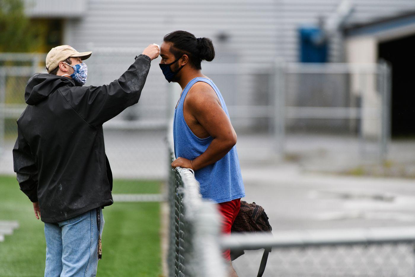 Bartlett head coach Chance Matsuoka checks the temperature of senior Edward Savelio at the start of practice on August 31, 2020. (Marc Lester / ADN)