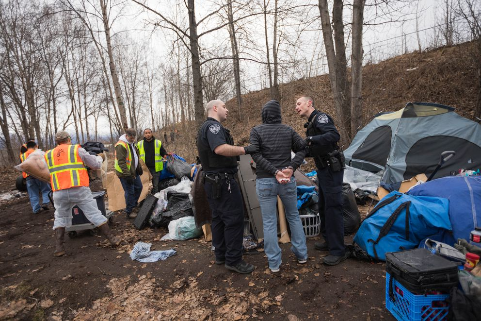 Anchorage police officers Casey Johnson, left, and Nicolas Ward handcuff Debra Martin as volunteers remove her belongings from a homeless camp near the Brother Francis Shelter on Saturday. Residents of the camp were served with a notice of abatement instructing them to move, and Martin had not moved by the deadline. She was released a short time later and continued to move her belongings. (Loren Holmes / ADN)