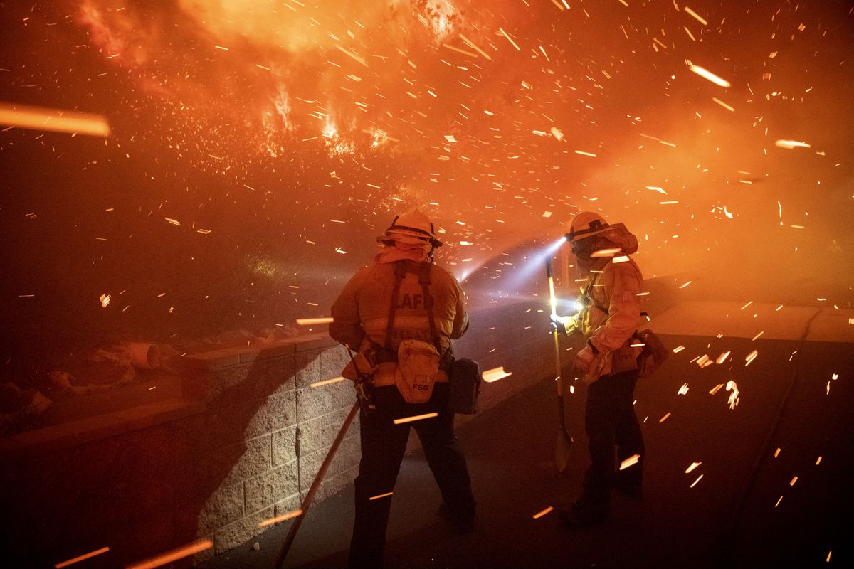 In this Thursday, Oct. 10, 2019 photo, embers from the Saddleridge fire blow by firefighters in Sylmar, Calif. (AP Photo/Michael Owen Baker)