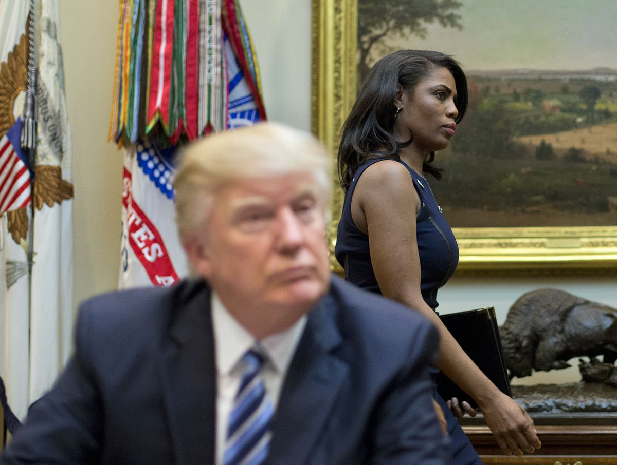 FILE - In this March 12, 2017 file photo, White House Director of communications for the Office of Public Liaison Omarosa Manigault, right, walks past President Donald Trump during a meeting on healthcare in the Roosevelt Room of the White House in Washington. Manigault Newman, who was fired in December, released a new book