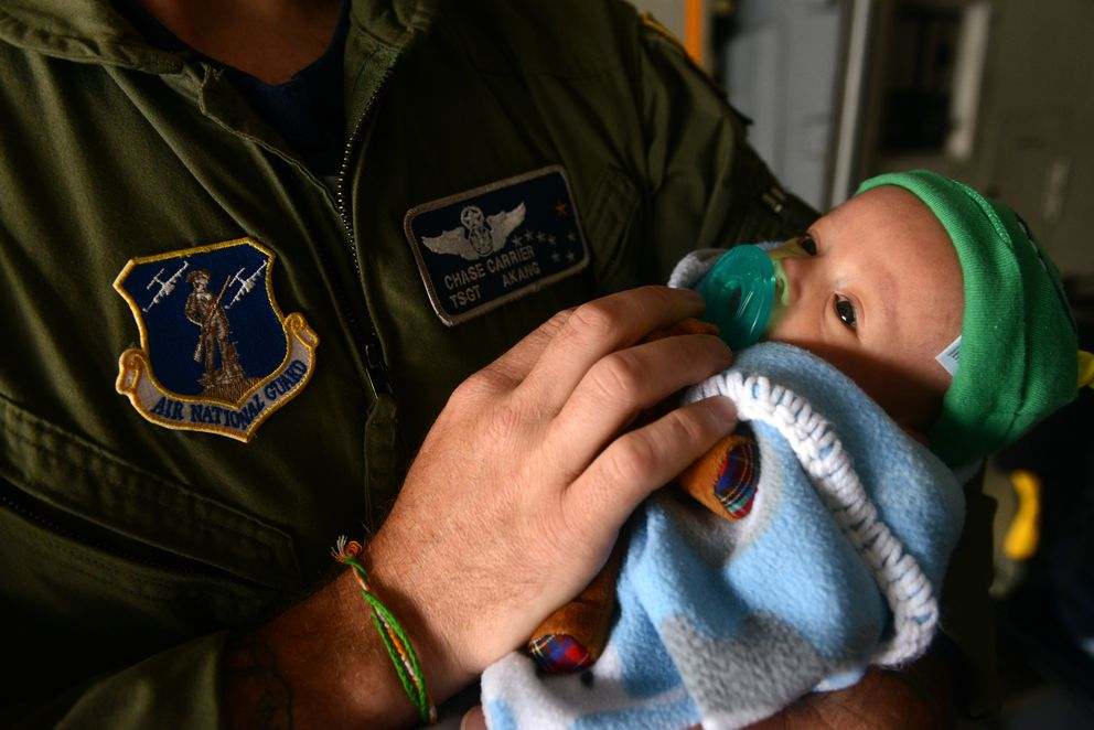 Chase Carrier holds his 6 week-old son Corbin during the Arctic Thunder air show on Saturday. Carrier is a C-17 loadmaster in the Air National Guard. (Bob Hallinen / Alaska Dispatch News)