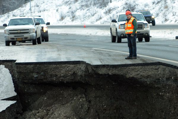 Chad Dugid of Mass Excavation Inc. surveys a section of damaged Glenn Highway on Friday, Nov. 30, 2018, following a large earthquake near Anchorage. (Matt Tunseth / ADN)