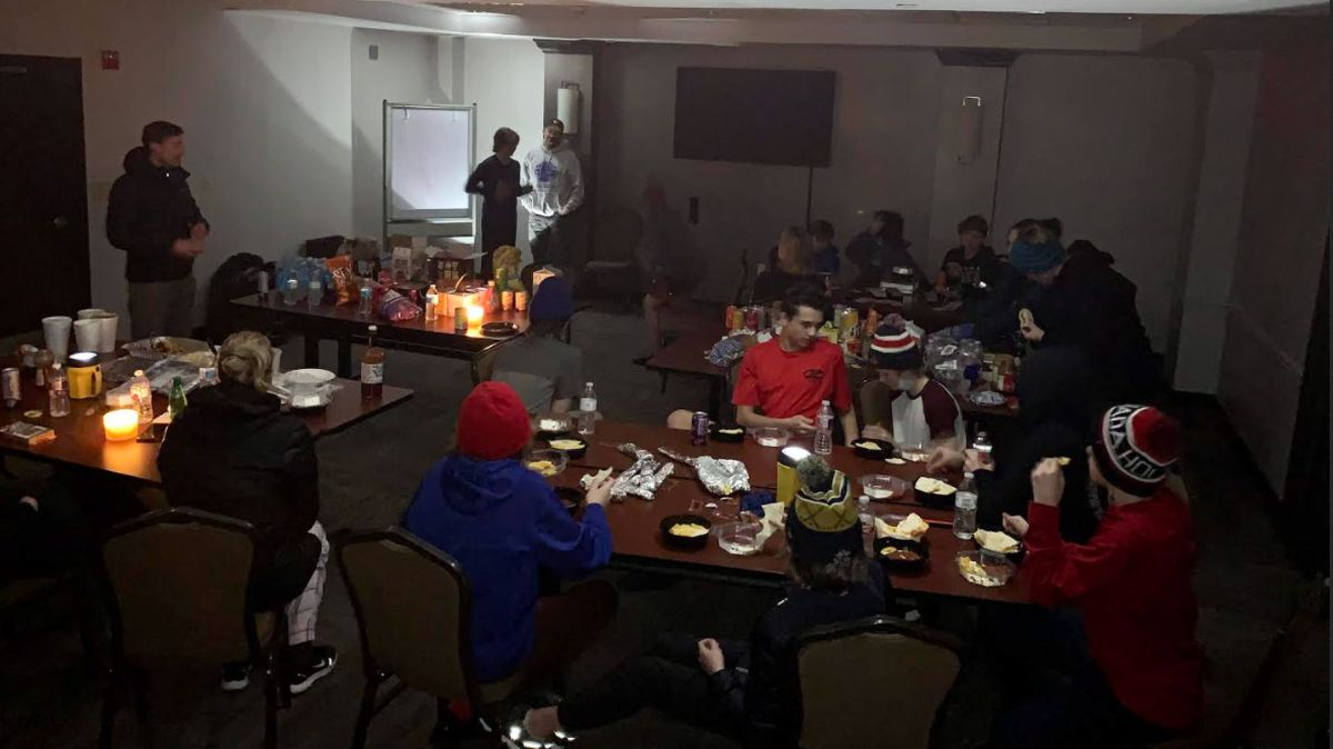 Members of the Alaska All Stars hockey team play charades and eat cheese quesadillas Monday in a darkened meeting room at the Hyatt Place in Austin, Texas. The hotel was without power for more than 30 hours. (Photo by Chris Heisten)