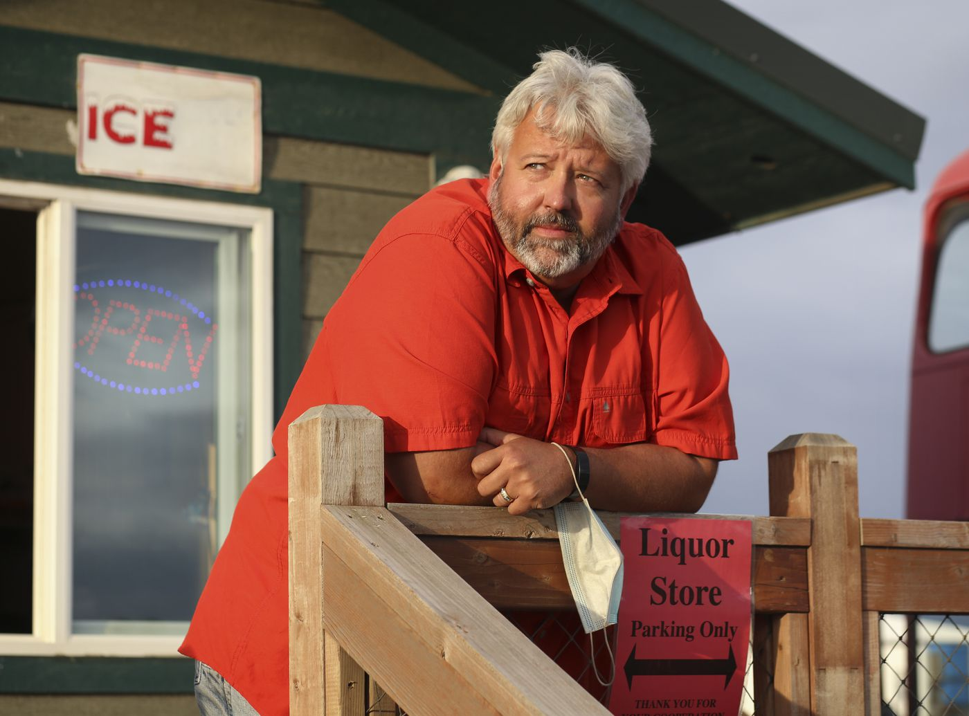 Employee Steve Fuson stands on the boardwalk outside Homer Liquor and Wine, on the Homer Spit, as he waits for customers on Aug. 8, 2020. Fuson, shaking his head, said business has been really slow in August. (Emily Mesner / ADN)