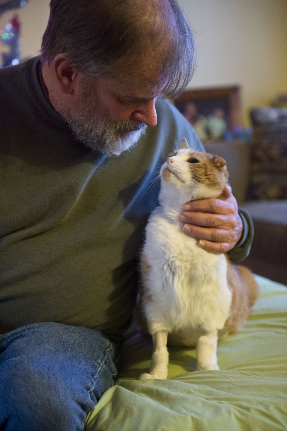 Bill Hess with his cat Carrizo at his Wasilla home on December 10, 2019. (Marc Lester / ADN)