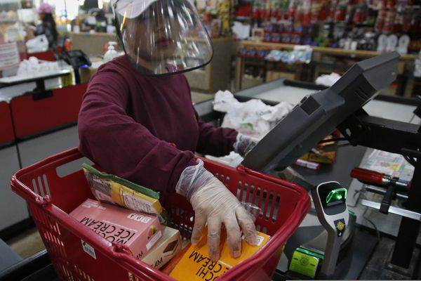 FILE - In this March 27, 2020, file photo, cashier Baby San wears a face shield and gloves as she scans items at grocery store Super Cao Nguyen, in Oklahoma City, due to concerns over the COVID-19 virus. Grocery workers across the globe are working the front lines during lockdowns meant to keep the coronavirus from spreading. (AP Photo/Sue Ogrocki, File)