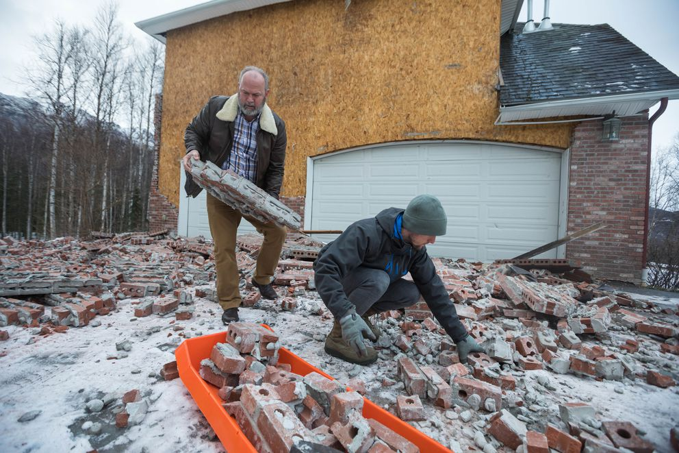Steve Baker, left, gets help cleaning up brick siding from his son Josh Baker, in Eagle River on Saturday, Dec. 1, 2018. Steve Baker's home was badly damaged during a strong earthquake that shook Southcentral Alaska in November 2018. (Loren Holmes / ADN)