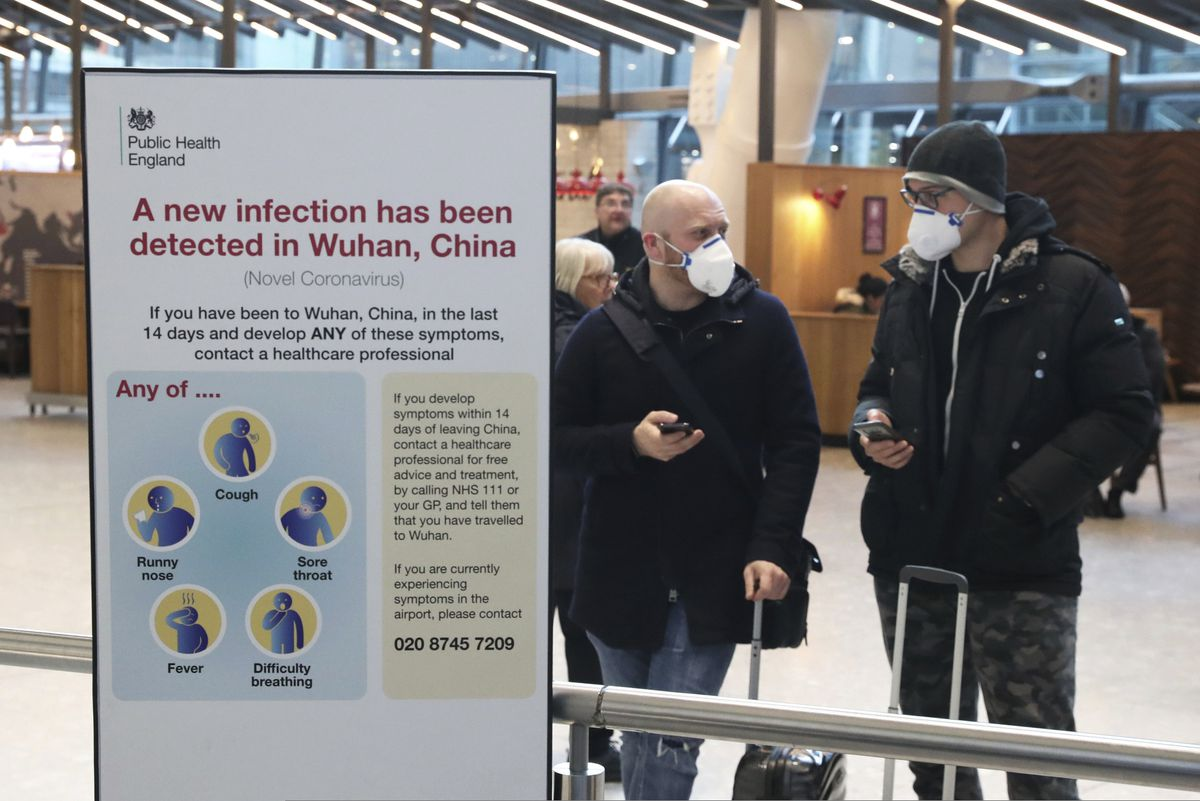 Passengers arrive at Heathrow Airport in London after the last British Airways flight from China touched down in the UK following an announcement that the airline was suspending all flights to and from mainland China with immediate effect amid the escalating coronavirus crisis, Wednesday Jan. 29, 2020. (Steve Parsons/PA via AP)