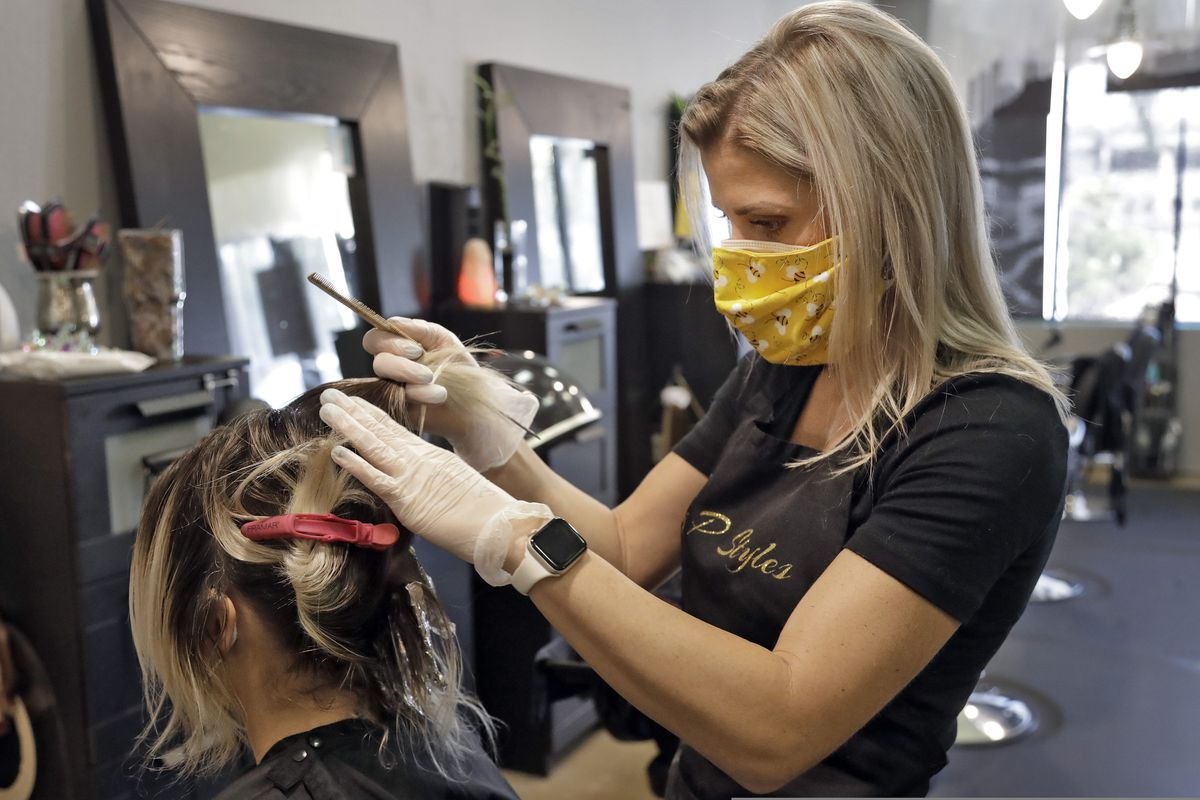 Priscilla Daughtry, of Pretty P Styles, does a hair coloring on a client Monday, May 11, 2020, in Clearwater, Fla. Hair and nail salons are allowed to reopen with rules to help stop the spread of the coronavirus. (AP Photo/Chris O'Meara)