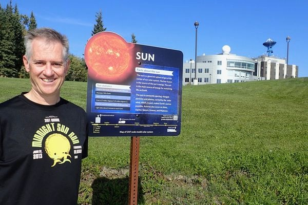 Space physics expert Peter Delamere at the start of the new Planet Walk at the University of Alaska Fairbanks. (Photo by Ned Rozell)