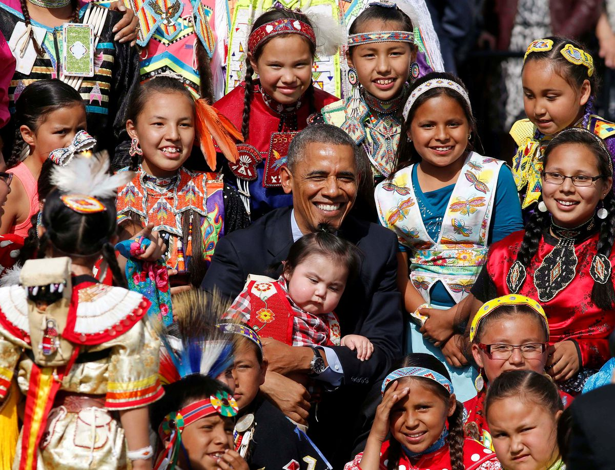 President Barack Obama holds a baby as he poses with children at the Cannon Ball Flag Day Celebration at the Cannon Ball Powwow Grounds on the Standing Rock Sioux Reservation in North Dakota, June 13, 2014. REUTERS/Larry Downing/File Photo