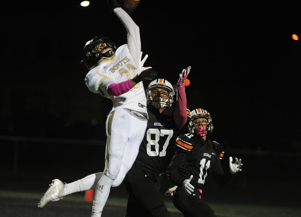 Aidan Ohlson, of South High, goes up to break up the pass intended for Marcus Faitele or Malyk Davis, of West High in a semifinal state football game at West High in Anchorage, AK on Friday, October 18, 2019. (Bob Hallinen photo)