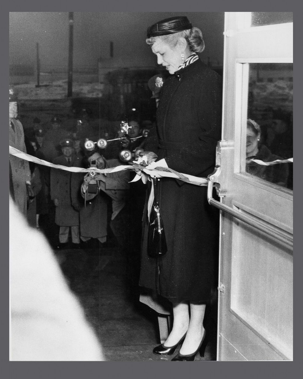 Willie Hodge, widow of Col. Hodge, cuts the ribbon at the opening of the Hodge Building in Whittier, now Begich Towers, in November, 1956. (Lundin Family Collection / PWS Museum)