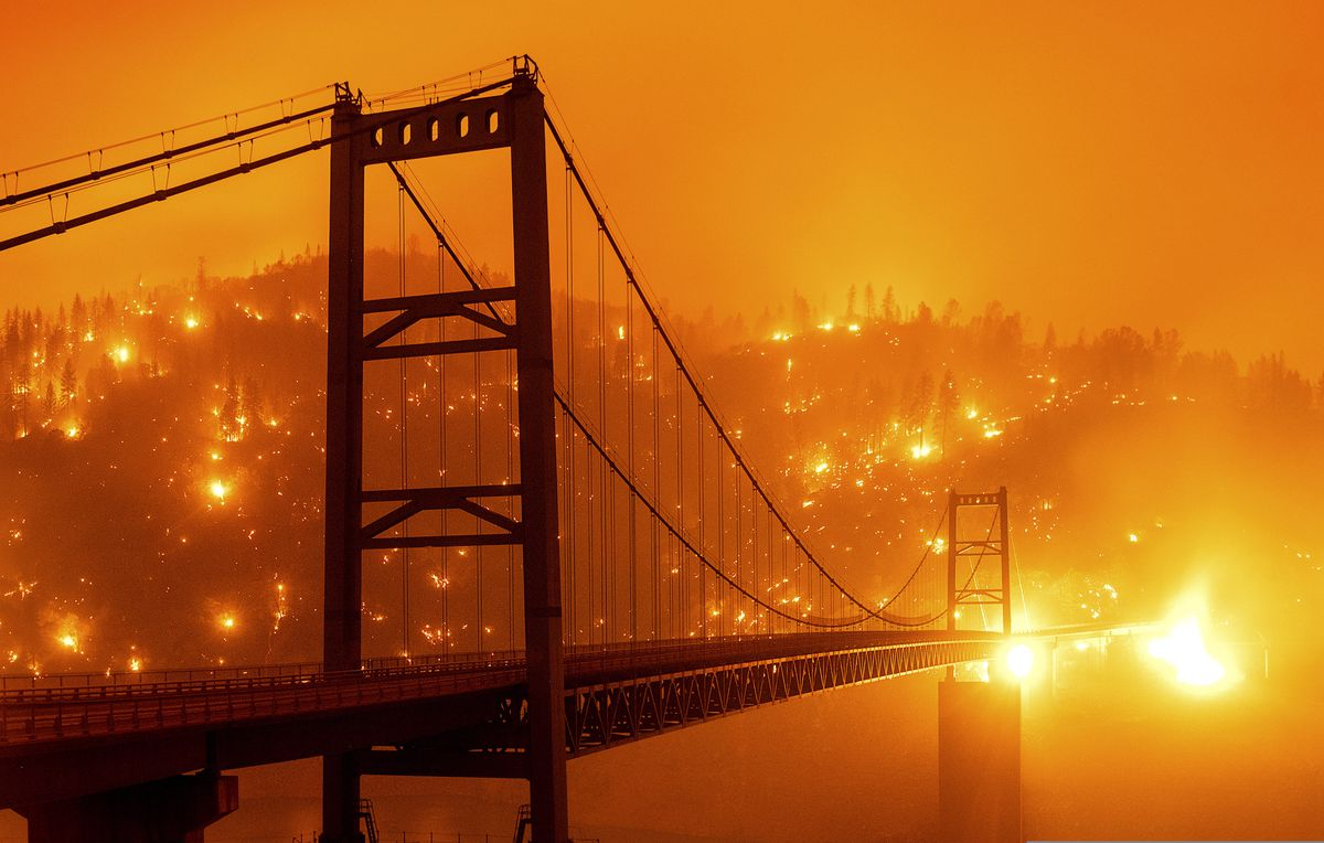 In this image taken with a slow shutter speed, embers light up a hillside behind the Bidwell Bar Bridge as the Bear Fire burns in Oroville, Calif., on Wednesday, Sept. 9, 2020. (AP Photo/Noah Berger)
